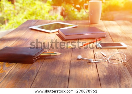 Country style technological composition. Suburban private yard wooden desk with essential items for creativity tablet PC smart phone musical headphones color pencils - stock photo