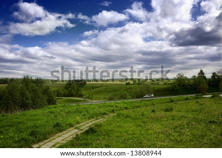 Country summer road through field and forest - stock photo