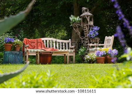 country sun drenched garden with a out door sitting area - stock photo
