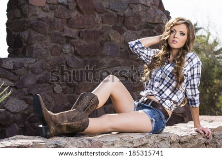 Country western girl posing in jeans and boots and wearing blue flannel shirt - stock photo
