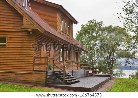 country wooden house in the forest close to lake - stock photo