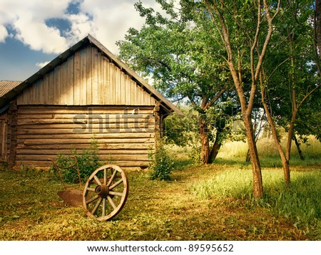 country yard with trees, wheel and plow - stock photo