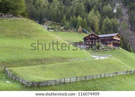 Countryside alp farm on the slope - stock photo
