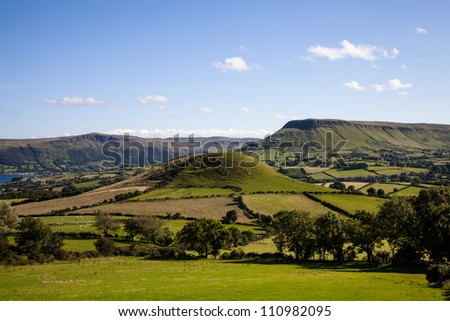 Countryside around the village of Cushendall in the Glens of Antrim, Ireland, under a summer sky.