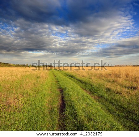 Countryside dirt road in steppe under nice cloudy sky - stock photo