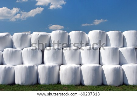 Countryside field with hay bale wrapped in plastic on sunny day - stock photo