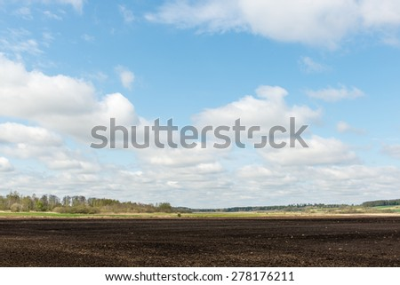 countryside fields in early spring with clouds and farmland