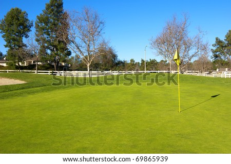 Countryside golf course with green grass, trees and wooden fence - stock photo