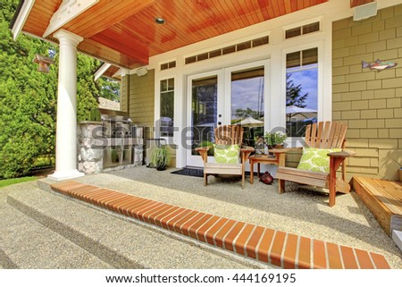 Countryside house exterior. View of column porch with chairs and concrete floor.