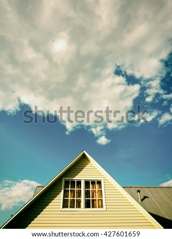 Countryside house roof against blue sky and cloud, vintage look - stock photo