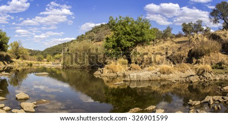 Countryside landscape scenic view of a fresh water stream on a natural park trail, in the Alentejo tourism destination region, Portugal.