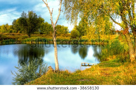 Countryside landscape with beautiful little lake. HDR image - stock photo