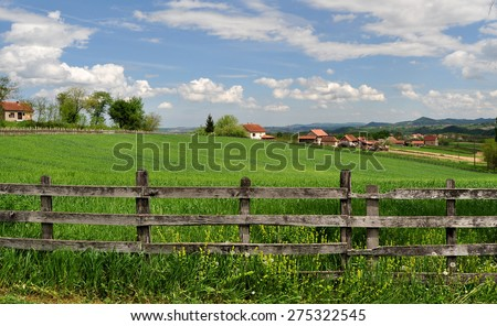 Countryside landscape with lush green grass and wooden fence - stock photo
