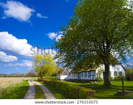 countryside old cottage with thatched roof in schleswig-holstein - stock photo