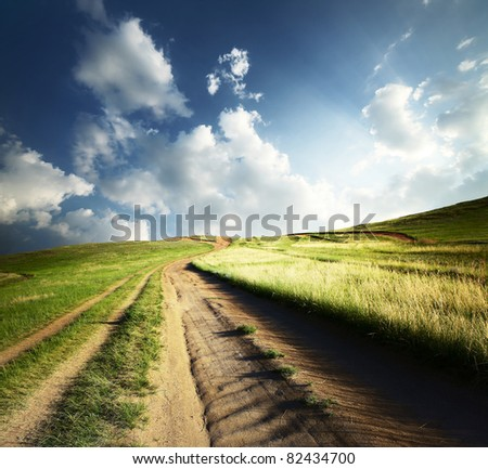 Countryside road leading to top of a hill at sunset light - stock photo