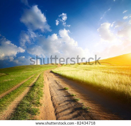 Countryside road leading to top of a hill at sunset light