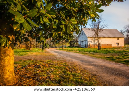 countryside road leads to a barn - stock photo