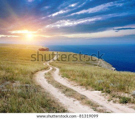 Countryside road near sea on sunset sky background - stock photo