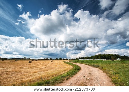 Countryside road with dramatic sky - stock photo