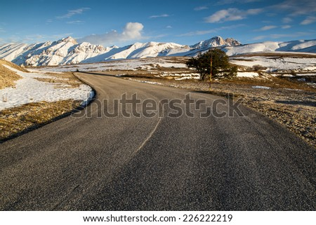 Countryside road with snowy mountain - stock photo