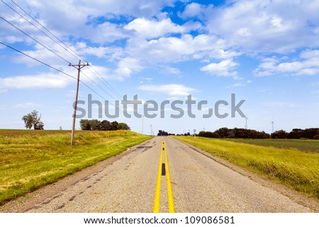 Countryside Road With Windturbines in the background - stock photo