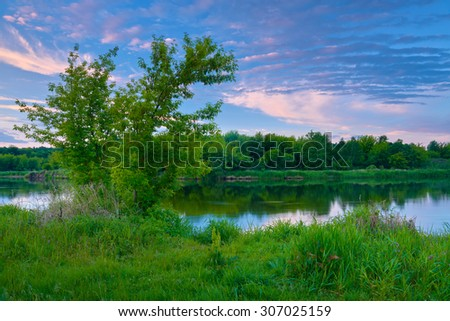 Countryside spring landscape blue sky trees clouds Narew river Poland dawn - stock photo