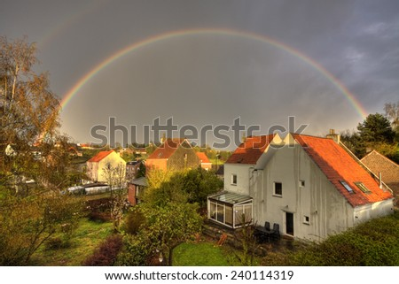 countryside town with rainbow - stock photo