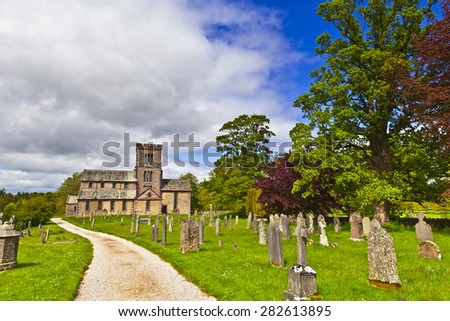 Countryside view with old road through graveyard to a rural church. - stock photo