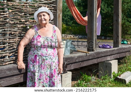 Countrywoman standing near summer veranda - stock photo
