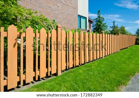 County style long wooden cedar yellow fence. - stock photo