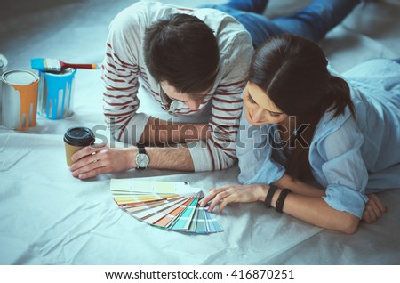 Couole choosing paint colour from swatch for new home lying on wooden floor - stock photo