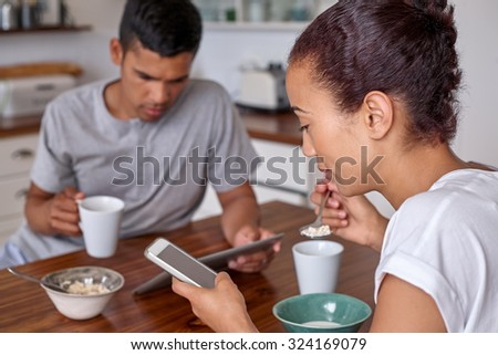 couple absorbed by their mobile devices, ignoring each other while having breakfast together in home kitchen - stock photo
