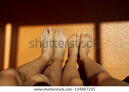 Couple acting naughty in bed - View of a couple's feet on the wall - stock photo