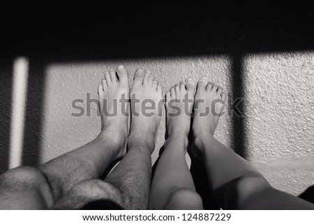 Couple acting naughty in bed - View of a couple's feet on the wall. Black and white - stock photo