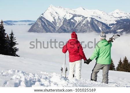 Couple Admiring Mountain View Whilst On Ski Holiday In Mountains - stock photo