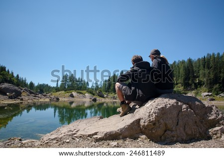 couple admiring the view by the lake after a hike in mountains, julijan alps, slovenia - stock photo