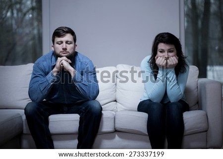 Couple after argument sitting on the sofa - stock photo