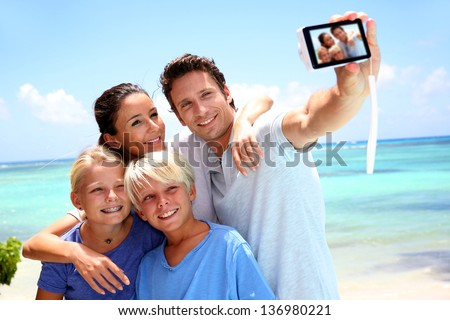 Couple and children taking family picture - stock photo