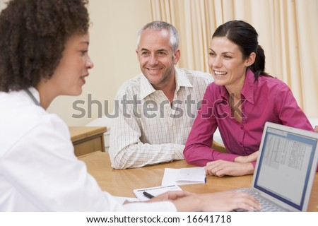 couple and doctor in office smiling - stock photo