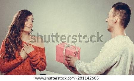 Couple and holiday concept. Handsome man surprising cheerful woman with gift box - stock photo