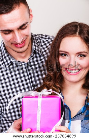 Couple and holiday concept. Smiling young man surprising cheerful woman with a gift box - stock photo