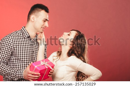 Couple and holiday concept. Smiling young man surprising cheerful woman with a gift box on red background - stock photo