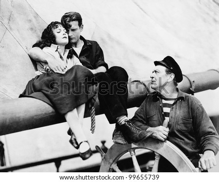 Couple and man steering sailboat - stock photo