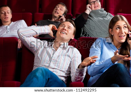 Couple and other people, probably friends, in cinema watching a movie, everybody is making a phone call, it seems to be a boring movie - stock photo
