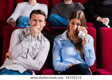 Couple and other people, probably friends, in cinema watching a movie; it seems to be a sad movie - stock photo