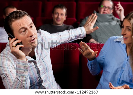 Couple and other people, probably friends, in cinema watching a movie, one is making a phone call and bothering the others - stock photo
