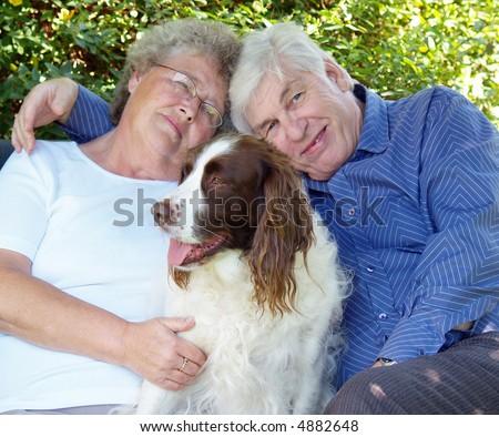 Couple and their dog english spaniel having a cuddle - stock photo