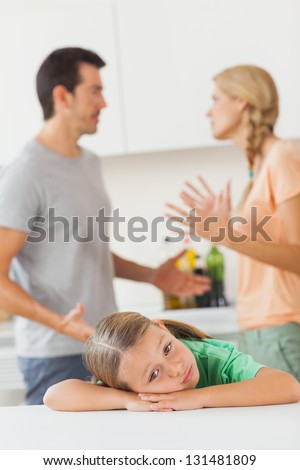 Couple arguing behind a sad girl in the kitchen