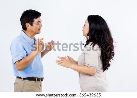 Couple arguing with each other against white background