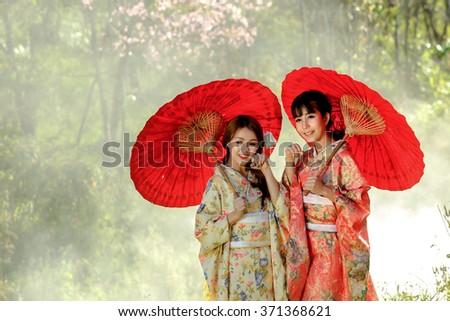 Couple asian women wearing traditional japanese kimono and red umbrella in the himalayan sakura garden,Thailand. - stock photo